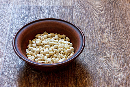Peanuts in a clay plate on a wooden table Banco de Imagens