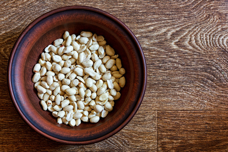 Peeled peanuts in an earthenware dish on a wooden table Banco de Imagens