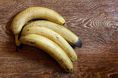 Four ripe bananas on a wooden table Banco de Imagens