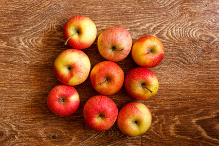 Nine red apples on a wooden table