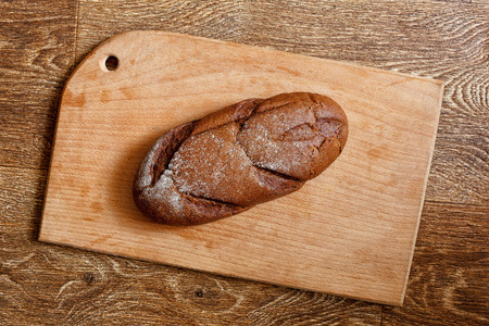 Loaf of bread on a chopping board. Wooden table.
