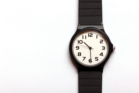 Classic uni-sexual black and white wrist watch on the white background, close up.