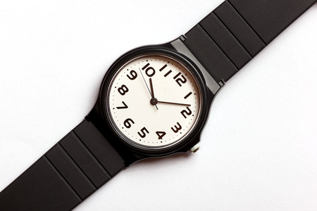Classic analog black and white wrist watch on the white background, close up.