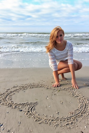 Teenager girl in a white dress draw heart on sand near beach sea Banco de Imagens