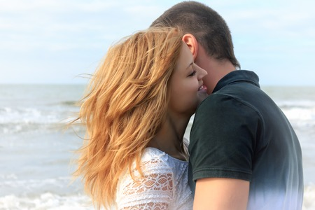 Blond and brunette teen couple hug together in beach outdoor at summer vacation. Sea waves on a background.