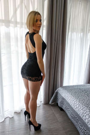 Young woman in extreme short little black dress posing near a window in her bedroom. Sexy girl with long legs and beauty ass in high heels going to a party. Stock Photo