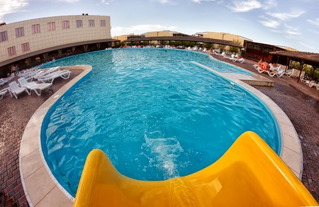 Kirillovka, Ukraine - August 28, 2016: Yellow water slide and a large swimming pool with blue water at the open-air