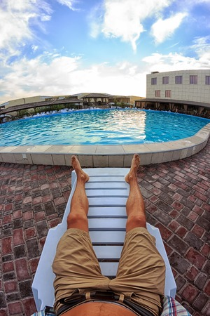 Kirillovka, Ukraine - August 28, 2016: Sunbathing by the hotel tourist resort swimming pool, mans legs lying down on a sunlounger looking over the water