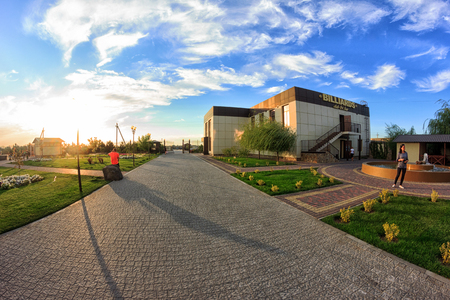 Kirillovka, Ukraine - August 28, 2016: Beautiful landscaping beach hotel: paths, lawns, the administration building and the sunset sky Editorial
