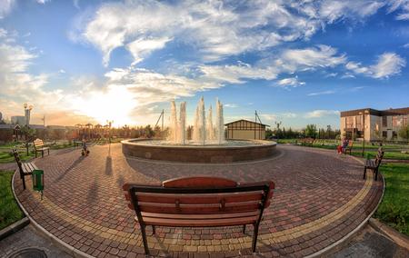 Kirillovka, Ukraine - August 28, 2016: Modern fountain in a beach hotel park. Wooden bench and playing children