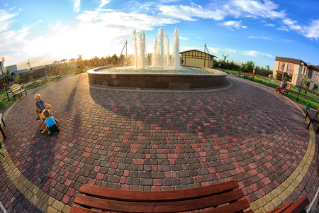 Kirillovka, Ukraine - August 28, 2016: Beautiful fountain in the park. Kids are playing. Wooden bench. Sunset in the sky.