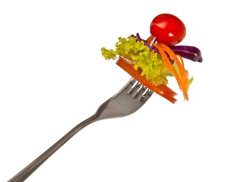 frische rote Tomaten und Salat auf einer Gabel. Isoliert