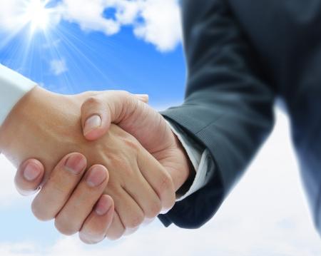 pacto: los hombres de negocios dándose la mano sobre fondo de cielo azul