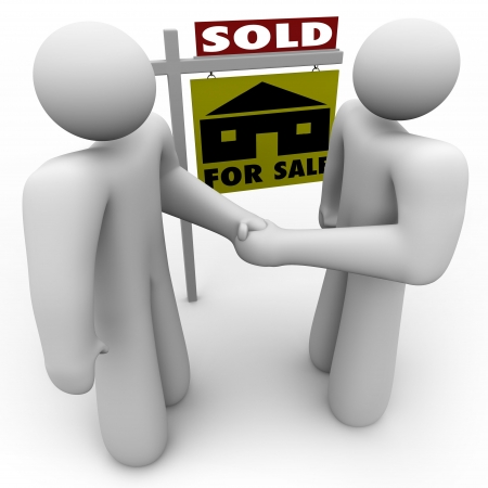 A home buyer and seller shake hands in front of a for sale sign that is marked Sold. Stock Photo