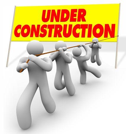 pull up: Un team lavora insieme per tirare su un segno di lettura Under Construction Archivio Fotografico