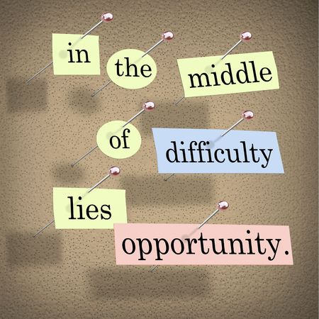 Pieces of paper each containing a word pinned to a cork board reading In the Middle of Difficulty Lies Opportunity Foto de archivo