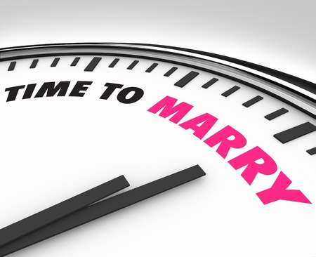White clock with words Time to Marry on its face, symbolizing the date of a marriage ceremony and celebration photo