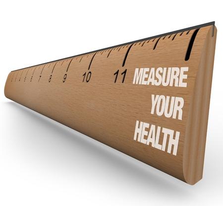 physical test: Un righello in legno con le parole di misura la salute, che simboleggia i benefici di intendere il vostro esercizio nutrizionale, dietetico e nel complesso sanitari obiettivi e progresso Archivio Fotografico