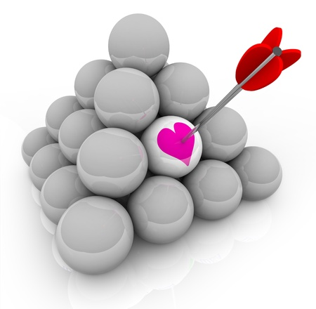 A pyramid of white balls with an arrow stuck in one that shows a pink heart, symbolizing the hunt for love and finding romance photo