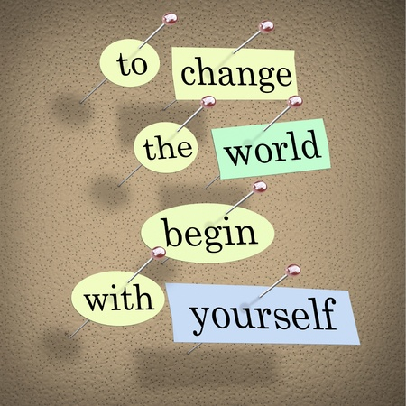 Pieces of paper each containing a word pinned to a cork board reading To Change the World Begin With Yourself Foto de archivo