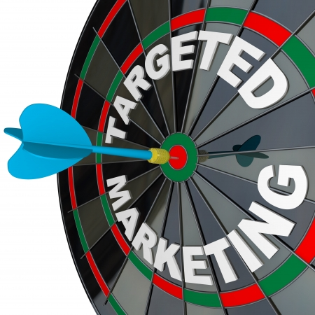 A blue dart hits a bulls-eye in the target on a dart board marked Targeted Marketing illustrating a successful advertising campaign that aims to reach a niche market photo