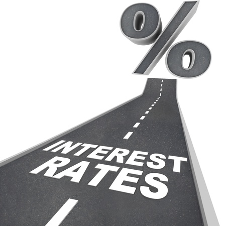 The words Interest Rates on a blacktop road and a percent sign at the top of the street, symbolizing the rising interest rates due to economic factors and conditions Stockfoto