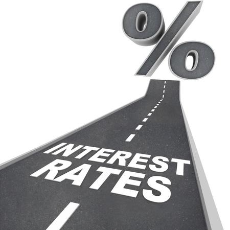 incremento: Las palabras las tasas de interés en una carretera de blacktop y un signo de porcentaje en la parte superior de la calle, simbolizando las aumento las tasas de interés debido a factores económicos y condiciones Foto de archivo