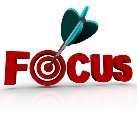 envision: An arrow makes a direct hit in the bulls-eye target in the word Focus, illustrating the importance of focusing and aiming at your goal Stock Photo