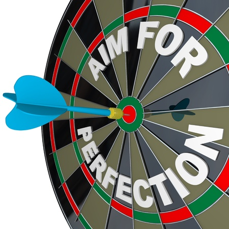 A dart hits a target bullseye on a dartboard surrounded by the words Aim for Perfection, representing the drive to succeed in sports, business and life, by giving every effort your best shot