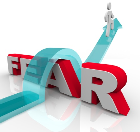 Un hombre salta sobre el miedo a la palabra sobre una flecha, ilustrando la valentía y el coraje necesarios para superar y vencer los temores y ansiedades Foto de archivo