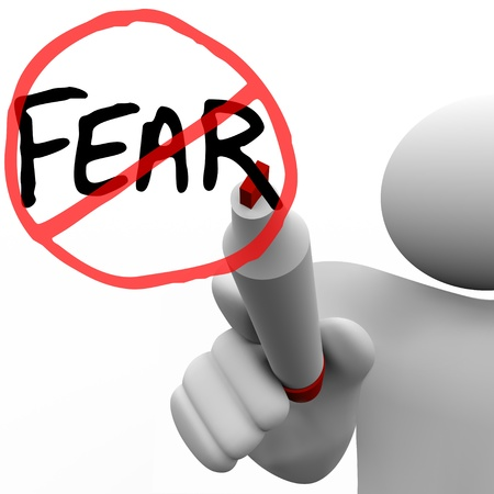 fear: A person draws the word Fear and a red circle and slash over it with a red felt marker on a glass board, illustrating the determination to conquer fears and anxieties