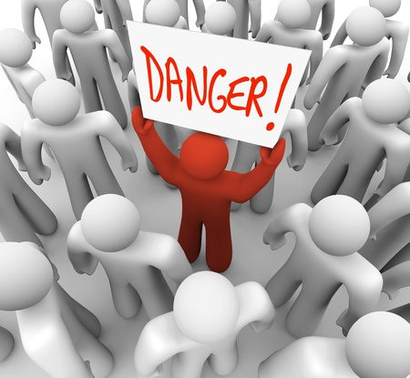 recognized: A red person stands out in a crowd holding a sign that reads Danger to warn and alert other people to a risk, hazard or other dangerous condition Stock Photo