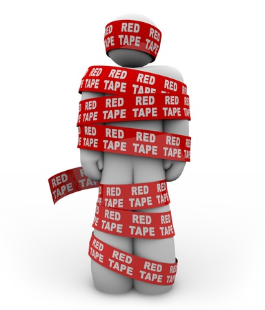 regulatory: A person is wrapped up in red ribbon with the words Red Tape repeated all over it, representing getting caught up in a mess of bureaucratic rules, regulations and procedures while trying to get something done