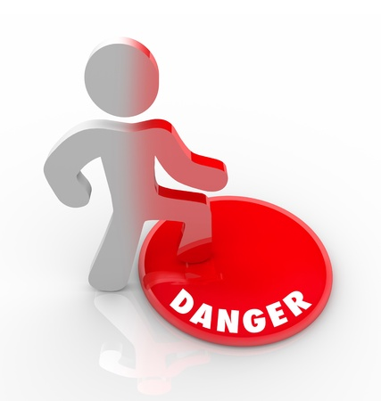 A person stands onto a red button marked Danger and is warned of hazardous conditions in the area photo