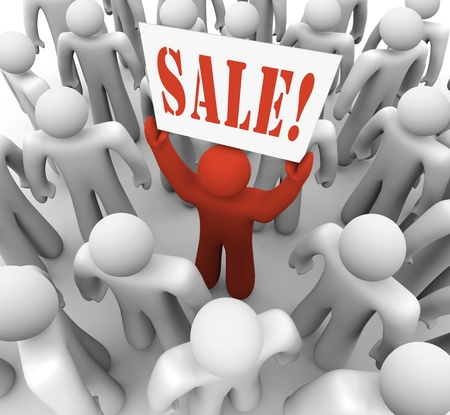 standout: A red person stands in a crowd holding a banner that reads Sale to advertise a special savings event at a store or shopping center Stock Photo