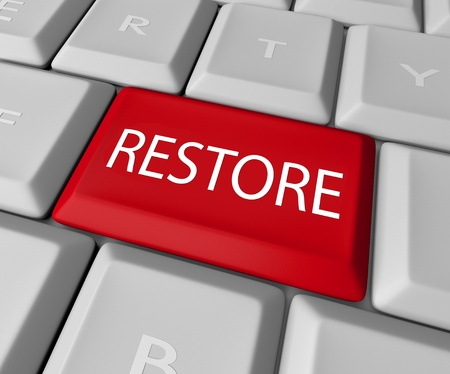 backing: A keyboard with a red key for the word Restore, representing the need to return to past values or recover files lost on a computer through a back-up copy Stock Photo