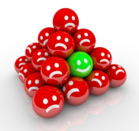 standout: One happy face in a pyramid of balls with sad, unhappy faces symbolizing a unique person in a good mood surrounded by grumpy, dissatisfied others Stock Photo