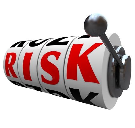 appears: The word Risk appears on slot machine wheels symbolizing the odds and danger of gambling, or investing your income in the stock market, bonds or other form of speculative investments Stock Photo