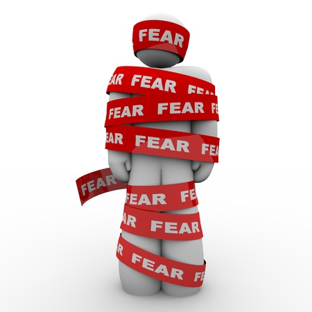fear: A man is wrapped in red tape reading fear representing the paralysis of being afraid and unable to move or act in the face of danger or something that scares or induces fright