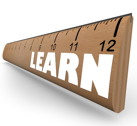 An old-fashioned wooden ruler with the word Learn illustrating the progress and growth in your education as measured in inches or feet photo