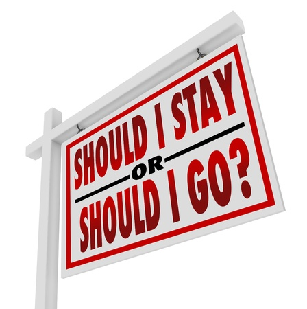 A white, wooden house for sale sign with the question Should I Stay or Should I Go, representing the uncertainty and indecision about changing a job or moving to a new home photo