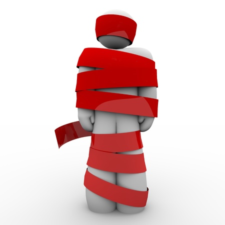 symbol victim: A man is wrapped in red tape representing being immobolized due to bureaucracy, kidnapping, fear or other concept keeping him from moving or acting Stock Photo