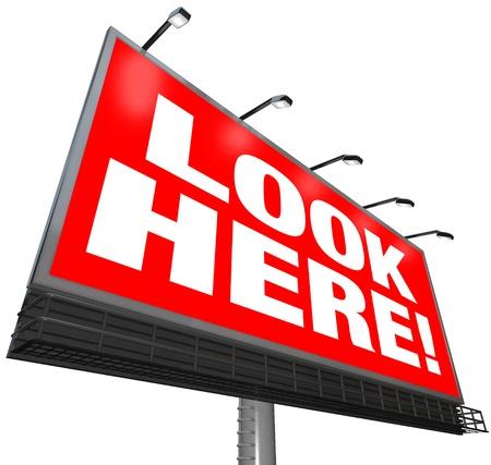 avviso importante: Le parole Look Here su uno sfondo rosso, su un grande cartellone esterno per attirare l'attenzione e pubblicizzare un messaggio o di lavoro o convincere la gente a notare un messaggio