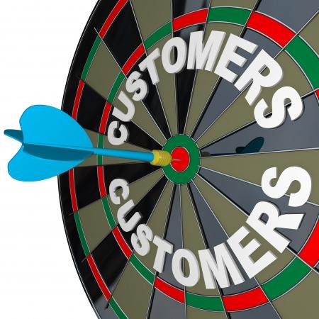 pr�cis: Une fl�chette bleue frappe un ?il de b?uf dans la cible sur un jeu de fl�chettes clients marqu�s pour symboliser trouver de nouveaux acheteurs pour vos produits ou services