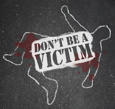A chalk outline of a dead body symbolizing someone who has been victimized by crime and the words Don't be a victim  Stockfoto