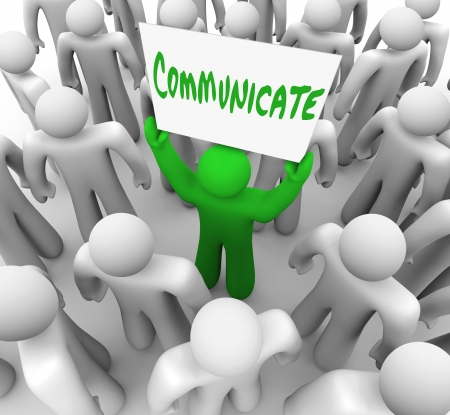 communicating: A green person stands in the middle of a crowd or audience and holds a sign reading Communicate to provoke a discussion or share an idea Stock Photo
