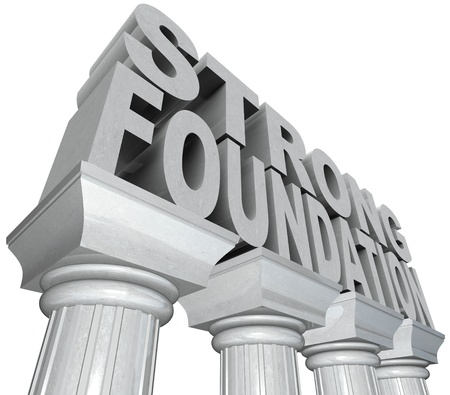 The words Strong Foundation in marble stone letters standing on white grantie pillars or columns to convey strength and resilience as well as historical power and experience