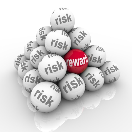 taking a risk: A pyramid of stacked balls each marked Risk with one reading Reward symbolizing the hidden benefits of taking a risk and overcoming a challenge with a great return on your investment of effort