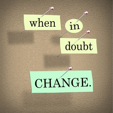 The words When in Doubt Change pinned to a cork bulletin board representing self-help improvement advice to motivate you to make positive changes in your life for success photo