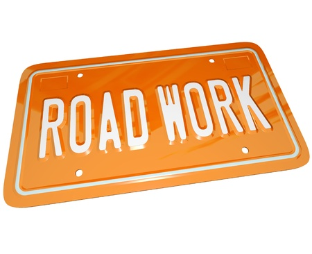 An orange metal license plate with the words Road Work communicating that there is roadwork ahead and construction is creating detours and traffic congestion Stock Photo